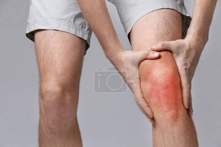 Photo for Young man suffering from knee pain on gray background. Health care concept - Royalty Free Image