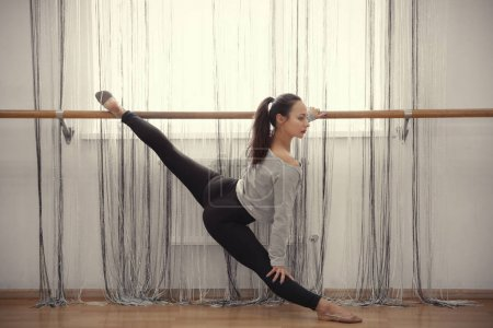 Young woman stretching near barre in dance studio...