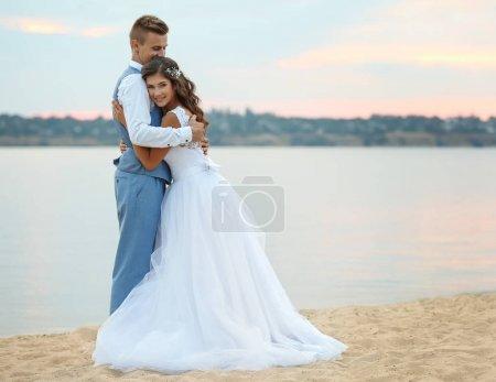 Photo pour Beau couple de mariage près de rivière - image libre de droit