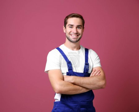 Handsome young worker on color background