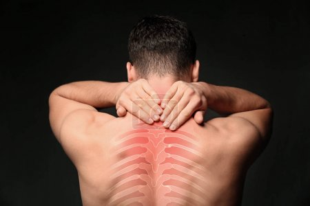 Young man suffering from neck pain on black background. Health care concept