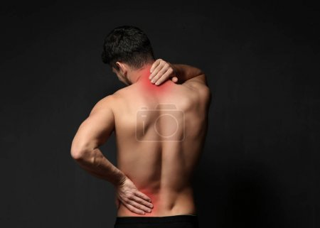 Young man suffering from back pain on black background. Health care concept