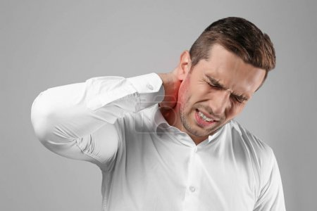 Young man suffering from neck pain on gray background. Health care concept