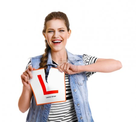 Young woman tearing learner driver sign on white background