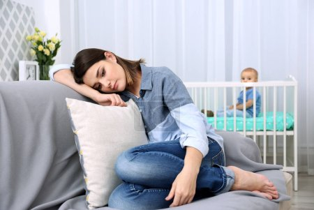 Depressed young woman sitting on sofa at home