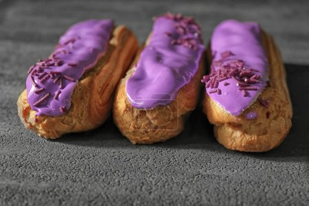 Photo for Delicious glazed eclairs on dark textured background - Royalty Free Image