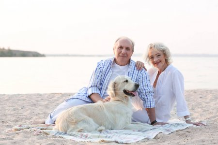 Senior couple and dog sitting on plaid