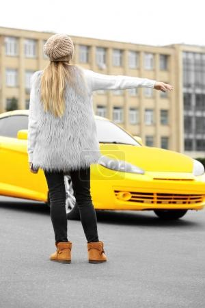 Woman catching yellow taxi