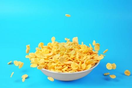 Photo for Bowl with corn flakes on blue background - Royalty Free Image