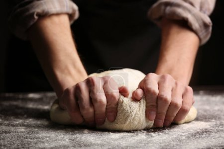 Male hands kneading dough