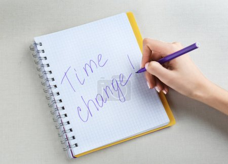 Female hand writing phrase TIME CHANGE in notebook...