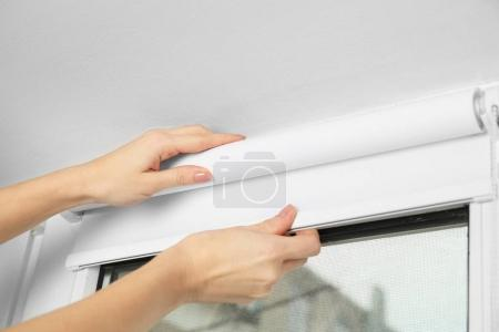 hands installing window blinds