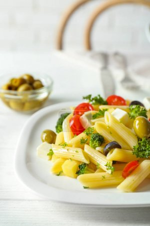 Photo for Pasta salad with tomatoes and olive on wooden table - Royalty Free Image