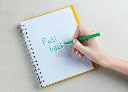 Foto de Mujer mano escribiendo frase caída hacia atrás en el cuaderno - Imagen libre de derechos