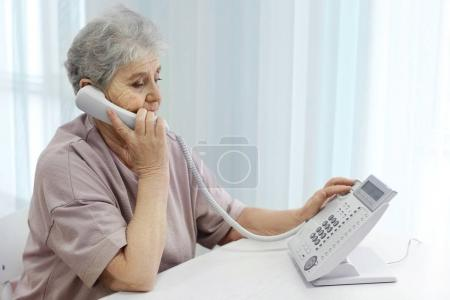 Elderly woman dialing telephone number