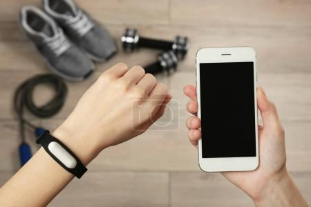 Female hands with fitness tracker and smartphone, closeup