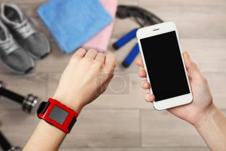 Female hands with heart rate monitor watch and smartphone, closeup