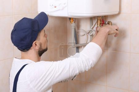 Plumber installing water heater in bathroom