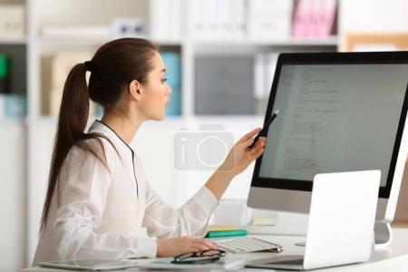 Photo pour Jeune femme travaillant au bureau - image libre de droit