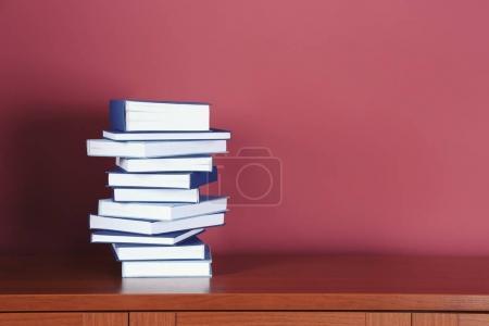 Photo pour Pile de livres sur la table en bois sur fond rose - image libre de droit