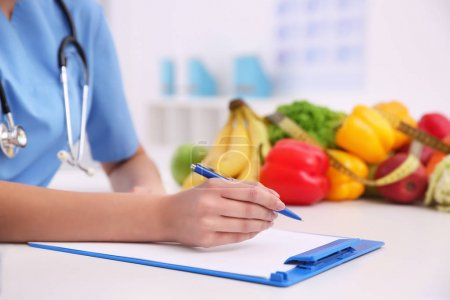 Young female nutritionist working in her office, closeup