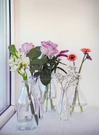 Glass vases with beautiful bouquets of flowers