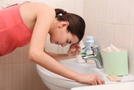Photo pour Jeune femme vomissant près de l'évier dans la salle de bain - image libre de droit