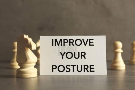 Photo for White paper with phrase IMPROVE YOUR POSTURE and chess pieces on gray table - Royalty Free Image