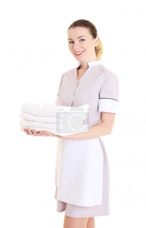 Attractive chambermaid holding pile of clean towel...