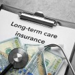 Text LONG-TERM CARE INSURANCE on clipboard with st...