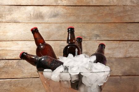 Bowl with bottles of beer in ice