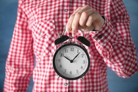 Female hands holding vintage alarm clock, closeup...