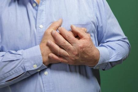 Elderly man holding hands on chest suffering from heart attack, closeup