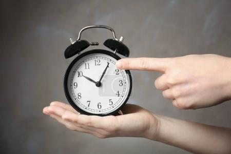 hands holding alarm clock