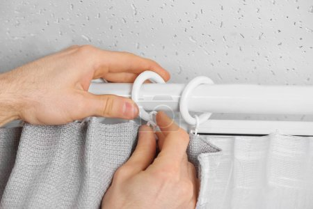 hands installing curtains