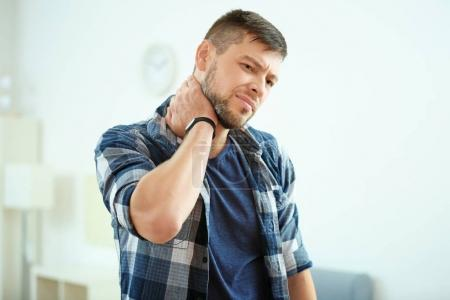 young man suffering from neck pain