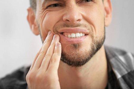 Photo pour Beau jeune homme souffrant de mal de dents, gros plan - image libre de droit
