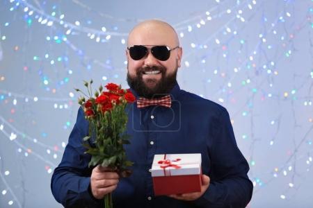 Photo pour Homme gras drôle avec boite et fleurs à la fête d'anniversaire - image libre de droit