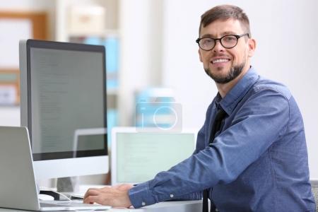 Photo pour Beau jeune programmeur travaillant au Cabinet - image libre de droit