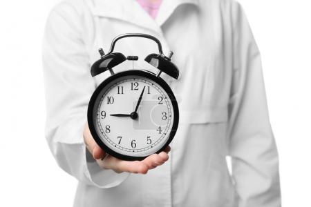 Photo pour Docteur tenant réveil sur fond blanc - image libre de droit