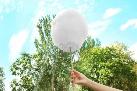 Photo for Female hand holding cotton candy, outdoor - Royalty Free Image