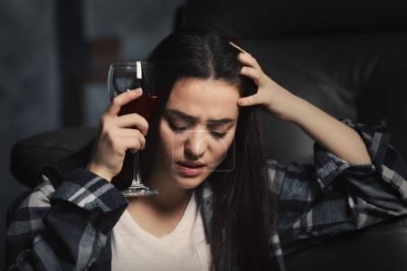 Depressed young woman drinking