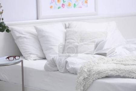 Photo pour Chambre intérieure avec lit et fleurs sur table de chevet - image libre de droit