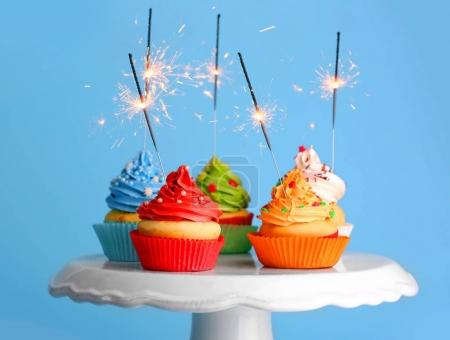 Delicious Cupcakes with sparklers on color backgro...