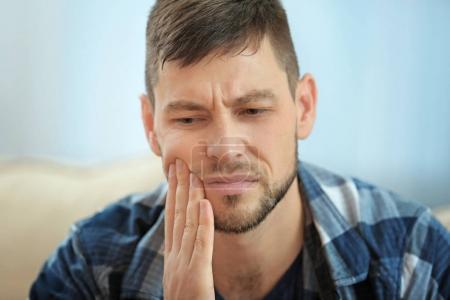 Photo pour Beau jeune homme souffrant de maux de dents à la maison, gros plan - image libre de droit