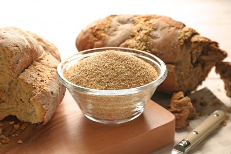Glass bowl of bread crumbs and broken loafs on wooden board