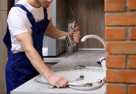 Handsome plumber in kitchen