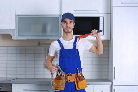 Photo pour Beau jeune plombier mâle dans cuisine - image libre de droit