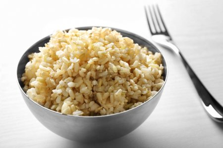 Photo for Bowl full of brown rice on white background - Royalty Free Image