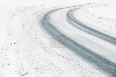 Traces of tires on snow covered road